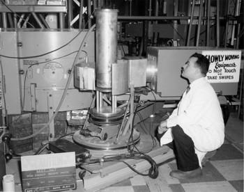 B.N. Brockhouse with the first version of his triple-axis spectrometer at the NRU reactor (November 1958 - July 1959). The cryostat carrying the specimen could be moved at half the scattering angle by a system of steel belts originally developed in 1947.